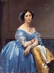 Princess Albert de Broglie wears a blue silk evening gown with delicate lace and ribbon trim. Her hair is covered with a sheer frill trimmed with matching blue ribbon knots. She wears a necklace, tasseled earrings and bracelets on each wrist.