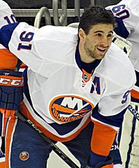 John Tavares in a white away New York Islanders jersey leaning forward and holding his hockey stick