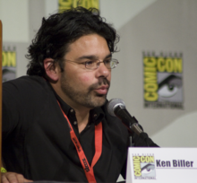 "A bearded, dark-haired man leans into a microphone; he is sitting behind a San Diego Comic Con paper placard that declares his name ""Kenneth Biller""."