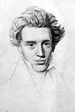 Portrait de face au crayon sur papier d'homme jeune chevelu. Le buste est esquissé, le fond est neutre.