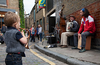 English: A boy with a toy trumpet in front of ...