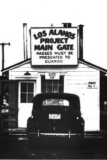 small guard shack with sign stating that passes must be presented to guards, a nineteen forties era car is parked there