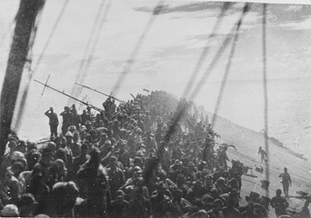 The crew of Zuikaku salute as the flag is lowered on the listing carrier after an airstrike. She was the last carrier participating in the attack on Pearl Harbor to be sunk. Lowering the flag on Zuikaku.jpg