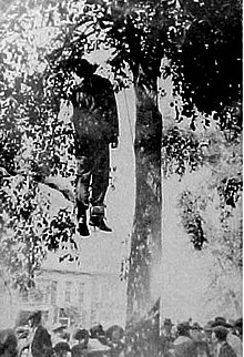 Man hanging by the neck from a tree