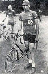 Photographie en noir et blanc d'un coureur cycliste se tenant debout à côté de son vélo.