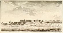Een fort met wallen met twee niveaus en vele bastions verheft zich boven de verre oever van een rivier.  In de buurt zijn enkele menselijke nederzettingen te zien.