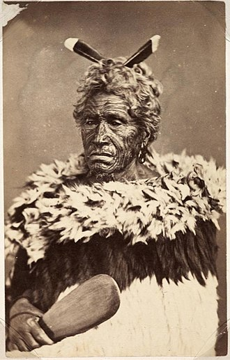 Māori culture - Traditional formal dress of the Classic/contact period. A dog skin cloak (kahu kuri), and holding a mere or patu (short edged weapon).