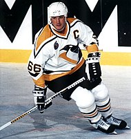 Photograph of Mario Lemieux holding a stick and skating