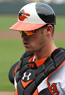 A baseball player wearing a white baseball jersey and black chest protector, both with orange trim, and a white-and-black baseball helmet with an orange brim and a cartoon bird on the face