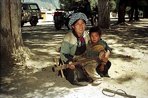 Woman with son busking in Lhasa, 1993.