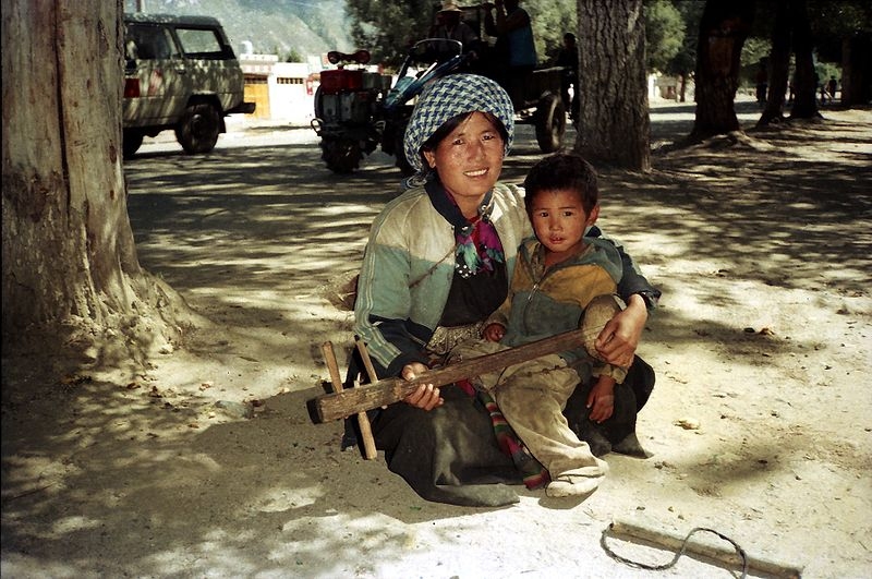 Ficheiro:Mother & son playing lute. Lhasa 1993.jpg