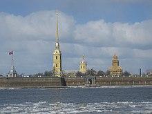 Photographie couleurs de quatre flèches de monuments dépassant d'un mur de forteresse devant un fleuve