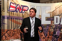 man in a suit holding a pint of beer standing in front of sign saying 'BNP VE Day'