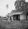Omsingelen en doorzoeken van huizen De patrouillecommandant wijst naar de de, Bestanddeelnr 15822.jpg