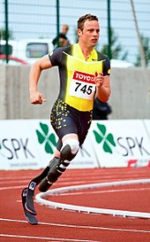 Photograph of Oscar Pistorius sprinting around a track with two carbon fibre transtibial artificial limbs.