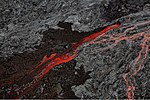 Aerial photograph of volcanic rock, with black cold lava split by a bright river of red lava