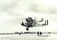 Military biplanes flying low over a field