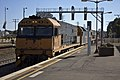 Pacific National (locos NR 76, AN7, NR 16 and NR 106) freight train passing Junee Railway Station.jpg