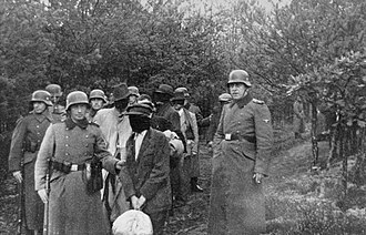 Polish civilians wearing blindfolds photographed just before their execution by German soldiers in Palmiry forest, 1940 Palmiry before execution.jpg