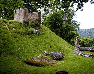 Coldrum Long Barrow - The eastern side of the monument, showing the surviving stone burial chamber at the top of the slope and fallen sarsens at the bottom