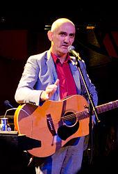 Kelly, 56 anni, è in piedi davanti a un microfono con la chitarra a tracolla.  Il suo braccio destro è piegato al gomito verso lo spettatore, mentre il suo sinistro è al fianco.  Indossa un abito grigio con una camicia arancione.