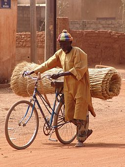 A man uses a bicycle to carry goods in Ouagadougou, Burkina Faso Person mit fahrrad feb07.jpg