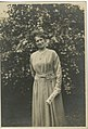 Photograph, black and white, of a woman standing in a garden. (16000851426).jpg