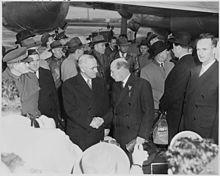 Truman schudt Attlee de hand.  Een grote menigte omringt hen.  Op de achtergrond staat een groot propellervliegtuig.