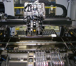 "SMT placement equipment - Internal details of a two head, gantry style pick-and-place JUKI SMT machine.  In the foreground are tape and reel feeders, then the (currently empty) conveyor belt for printed circuit boards, and in back are large parts in a tray.  The gantry carries two pickup needles, flanking a camera (marked ""do not touch"" to avoid fingerprints on the lens)."