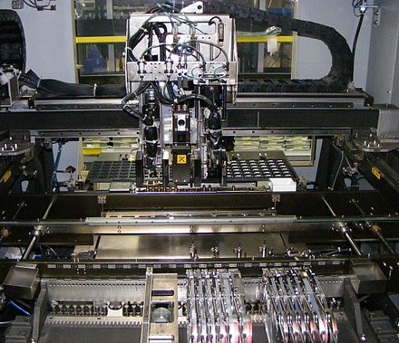 "Internal details of a two head, gantry style pick-and-place JUKI SMT machine. In the foreground are tape and reel feeders, then the (currently empty) conveyor belt for printed circuit boards, and in back are large parts in a tray. The gantry carries two pickup needles, flanking a camera (marked ""do not touch"" to avoid fingerprints on the lens). Pick and place internals of surface mount machine.JPG"