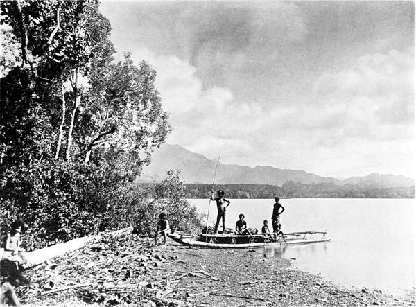 Black and white photograph of three men and two children with a canoe moored on a beach.  Trees and driftwood line the beach.  In the background, across the water, more land and mountains can be seen.