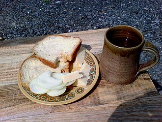 Ploughman's lunch - A ploughman's lunch consisting of bread, butter, sliced onion, wedges of cheese, and a mug of ale