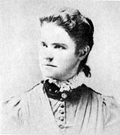 A washed-out monochrome photograph portrait of a young woman with shoulders squared to the camera, the head turned to the left, a neutral-colored dress topped by a dark ruff and white lace, the woman's dark hair pulled back behind her ears to fall down below her collar