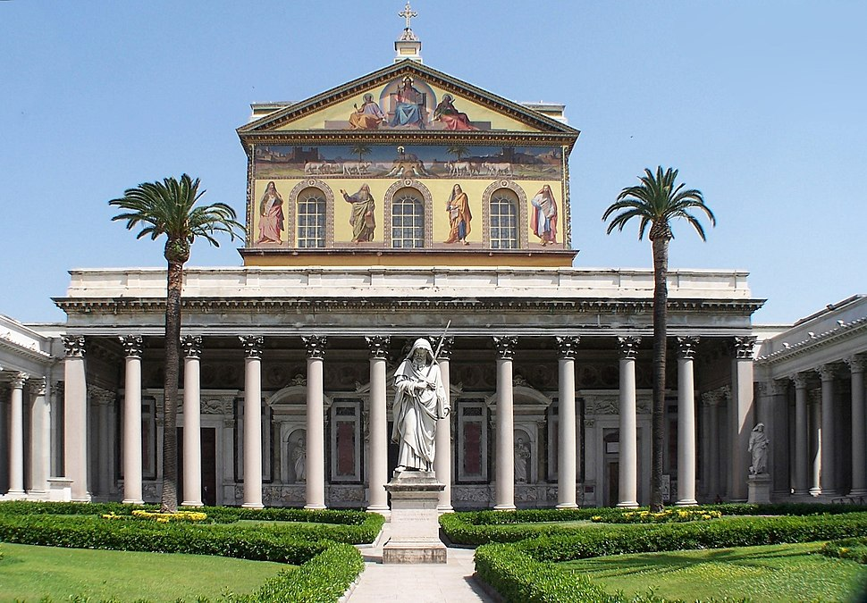 A courtyard with palm trees and a greater-than-lifesized statue of St. Paul holding a sword in front of the colossal portico of the basilica and a large mural covering the upper facade