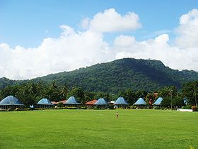 Round Samoan houses with blue roofs, Lepea village with Mt Vaea beyond.JPG