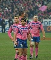 Au premier plan quatre joueurs sont statiques lors d'un temps mort, vêtus de rose et de bleu. Au fond, on devine les spectateurs parisiens avec les mêmes couleurs en tribune.