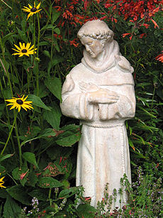A garden statue of Francis of Assisi with birds