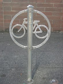 A ring with a stylized bicycle inside, with riveted to a post (running through the ring), all of galvanized metal. It is set in a concrete slab in front of a brick wall.