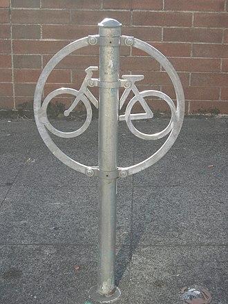 Кольцо со стилизованным под велосипед внутри, с приклепанной к стойке (проходящей через кольцо), все из оцинкованного металла. Он установлен в бетонной плите перед кирпичной стеной.