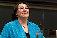 A colour photo of Sheila Watt-Cloutier, looking up and smiling, while giving a lecture at York University. She is a wearing a blue jacket over a black shirt and has an ulu necklace.