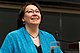 """A colour photo of Sheila Watt-Cloutier, looking up and smiling, while giving a lecture at York University. She is a wearing a blue jacket over a black shirt and has an ulu necklace."""