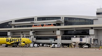 Dallas/Fort Worth International Airport - A Skylink train making a stop at Terminal E, next to a Spirit Airlines Airbus A320.