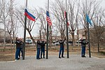 Soyuz MS-11 crew and backup crew raise flags.jpg
