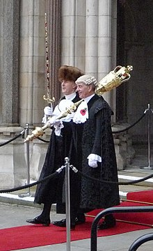 Two men in black cloaks walking side by side on a red carpet. One wears a fur hat and carries a sword in a red and gold scabbard upright. The other wears a judge's wig and has a large, gold mace over his left shoulder.