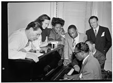 Jack Teagarden, Dixie Bailey, Mary Lou Williams, Tadd Dameron, Hank Jones et Milt Orent autour de Dizzy Gillespie au piano, dans l'appartement de Mary Lou Williams.