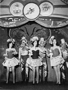 Three women and three men on stage in a chorus number