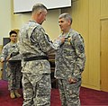U.S. Army Brig. Gen. Stephen Farmen, the commanding general of the 19th Expeditionary Sustainment Command, presents the Legion of Merit to Col. Mark Weinerth, outgoing commander of the 501st Sustainment Brigade 140627-A-NY467-009.jpg