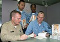 US Navy 021216-N-1711I-001 A trio of USS Wasp (LHD 1) sailors wait patiently to purchase an autographed copy of Aviation Structural Mechanic 1st Class John Heatherly's debut book entitled.jpg