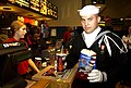 US Navy 031106-N-9693M-001 Seaman Apprentice Chris Firking carries popcorn and soda into a theater.jpg