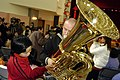 """US Navy 040226-N-7923C-003 Musician 3rd Class Patrick Curry, a tuba player with the Seventh Fleet Band's brass quintet """"The Shonan Brass"""" gets help playing his instrument from a Chinese child at the Shanghai Children's Home.jpg"""